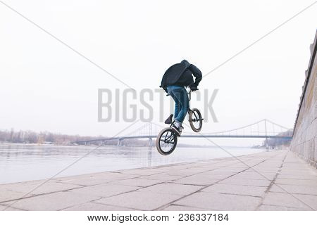 A Stylish Man Makes Stunts On A Bmx Bike In The Outdoors. Freestyle On Bmx