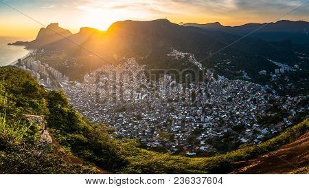 Panoramic View Of Rocinha, The Largest Favela In Rio De Janeiro City, By Sunset Behind Mountains