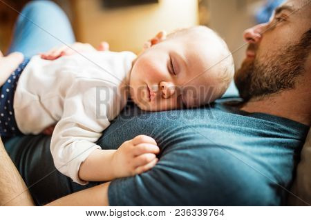 Father With A Baby Girl At Home, Sleeping On The Sofa. Paternity Leave. Close Up.