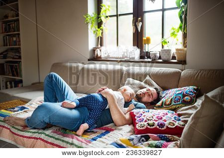 Father With A Baby Girl At Home, Sleeping On The Sofa. Paternity Leave.