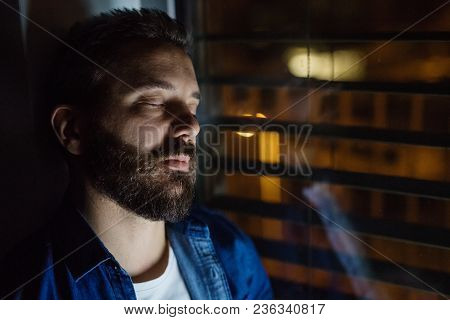 A Handsome Man Slepping By The Window At Home At Night. Close Up.