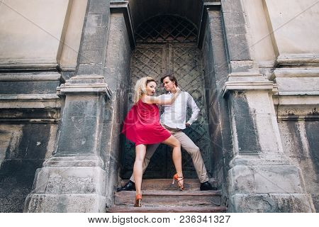 Beautiful Happy Couple In Love Embracing And Dancing At Old Building In Sunny Street. Stylish Hipste