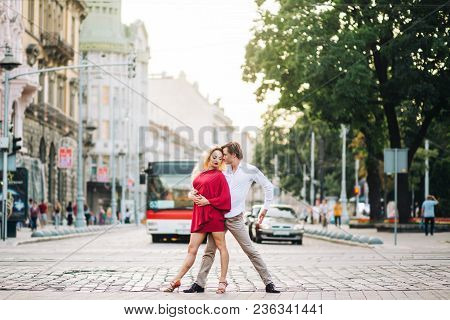 Beautiful Happy Couple In Love Embracing And Dancing In Evening Sunlight In Sunny Street. Stylish Hi