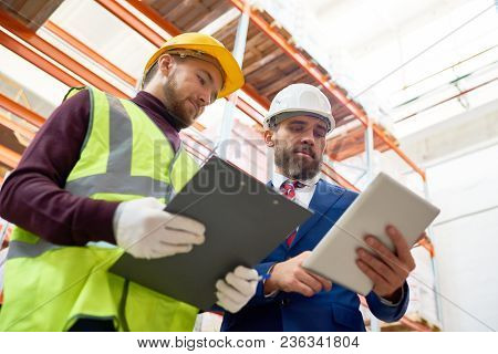Low Angle Portrait Of Mature Businessman Wearing Hardhat Using Digital Tablet And  Talking To Worker