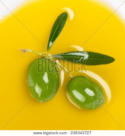 Small Twig Of Olive Tree With Green Olives And Leaves In A Puddle Of Olive Oil.