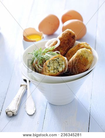 Crunchy Breaded Egg Patties Shallow Fried And Served With Onion Salad.
