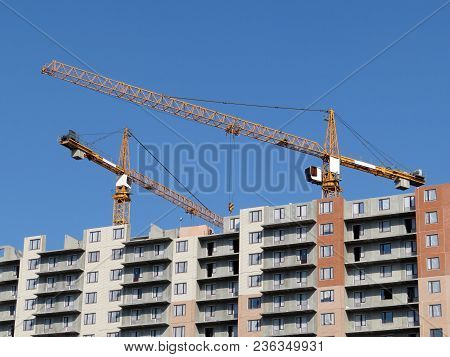 Construction Site. Tower Cranes Over The Panel Building Under Construction, Unfinished House