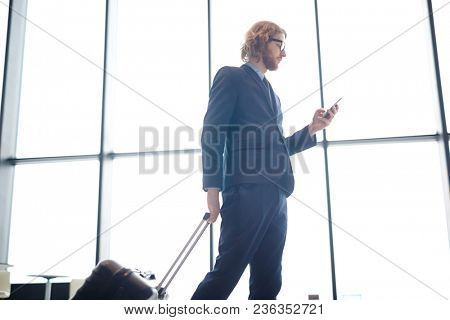 Young man in elegant suit messaging in smartphone and pulling suitcase while walking to flight station