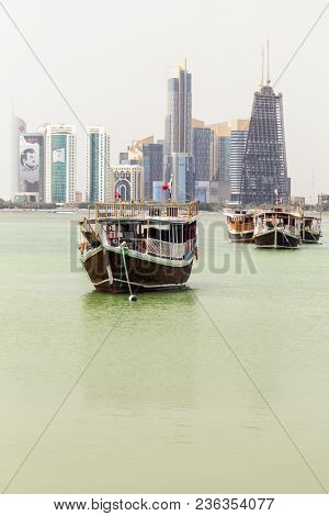 DOHA, QATAR - April 16, 2018: Dhows in Doha bay, against the towers bearing images of Emir Tamim bin Hamad al-Thani. The economic siege of Qatar by its neighbours has boosted patriotism.