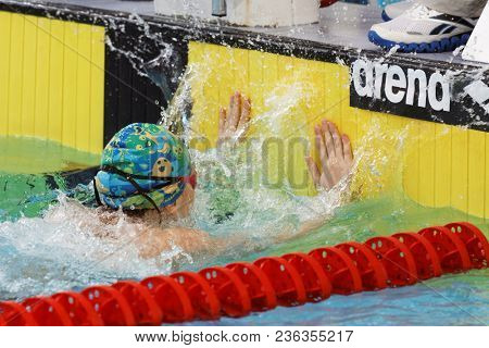 ST. PETERSBURG, RUSSIA - APRIL 11, 2018: Girl on finish in 4x50m breaststroke relay swimming during All-Russian Swimming Competitions Merry Dolphin. The competitions was founded in 1965