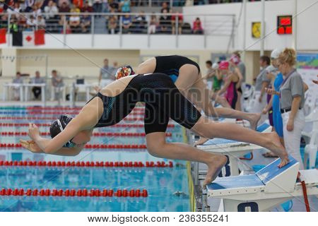 ST. PETERSBURG, RUSSIA - APRIL 11, 2018: Girls start in 4x50m breaststroke relay swimming during All-Russian Swimming Competitions Merry Dolphin. The competitions was founded in 1965