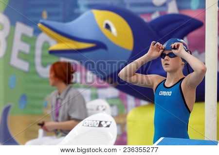 ST. PETERSBURG, RUSSIA - APRIL 11, 2018: Girl prepares for start in 4x50m breaststroke swimming relay during All-Russian Swimming Competitions Merry Dolphin. The competitions was founded in 1965