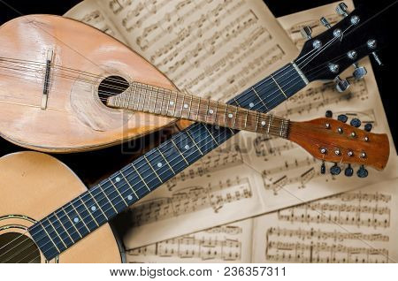 Mandolin And Guitar With Blurred Sheet Music Books In The Background. Stringed Musical Instruments.
