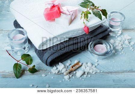 Spa Setting On Blue Wooden Rustic Table. Natural Sea Salt, Candles, Handmade Soap, Flowers, Towels.