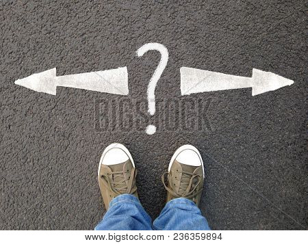 Feet In Canvas Shoes Standing On Asphalt From Personal Perspective, Road Markings With Arrows Pointi