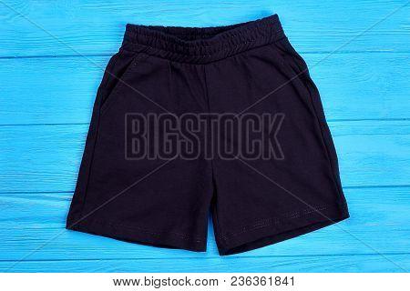 Fabric Dark Shorts For Kids. Cotton Shorts For Baby On Blue Wooden Background. Children Summer Appar