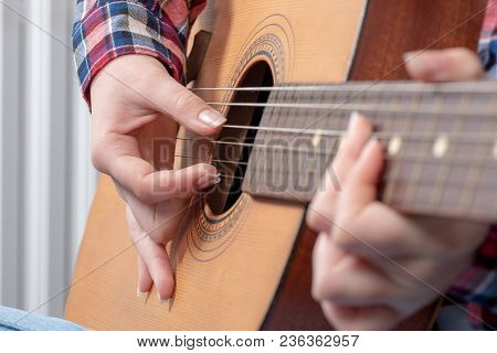 Close-up Of A Young Woman's Hands Playing Guitar