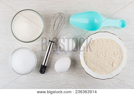Oat Flour, Chicken Eggs, Sugar, Salt, Spoon And Whisk On Wooden Table. Top View