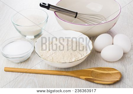 Oat Flour, Bowl With Whisk, Sugar, Salt, Bamboo Spoon, Chicken Eggs On Wooden Table