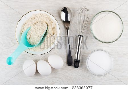 Different Ingredients For Preparing Oat Pancakes, Spoon And Whisk On Wooden Table. Top View