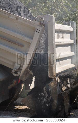 The Machine Unloads Hot Asphalt To Repair Roads