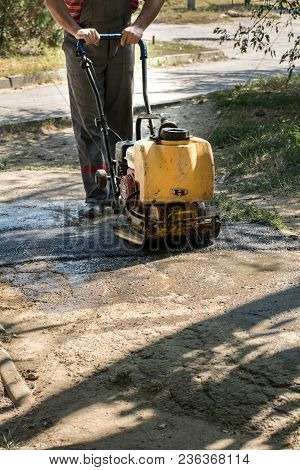 Road Repair Details. A Worker With A Manual Paver Aligns The Hot Asphalt On The Road.
