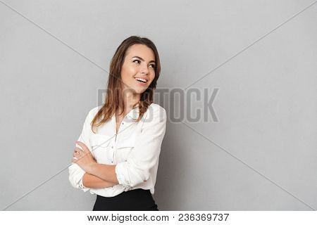 Image of an amazing young business woman standing isolated over grey wall background looking aside.