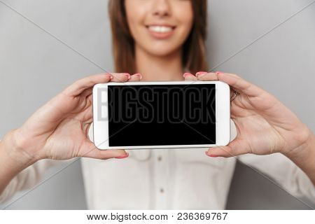 Cropped image of cheerful young business woman standing isolated over grey wall background showing display of mobile phone.