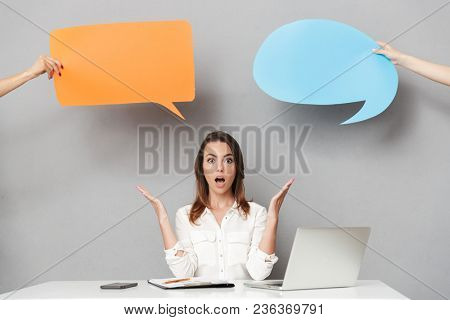 Image of a shocked young business woman sitting isolated over grey wall background using laptop computer near speech bubbles.
