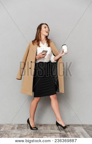Image of happy young business woman standing isolated over grey wall background holding coffee chatting by phone.