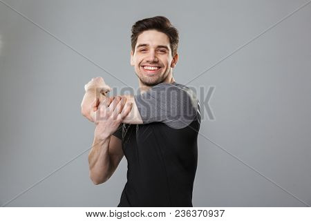 Portrait of a smiling young sportsman warming up isolated over gray background