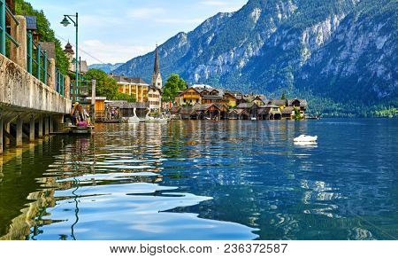 Hallstatt, Austria. Lake Hallstattersee with calm blue water among austrian Alps mountains. Embankment of antique picturesque town. View to old houses on coast and chapel of church.