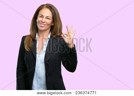 Middle age business woman doing ok sign with hand, approve gesture
