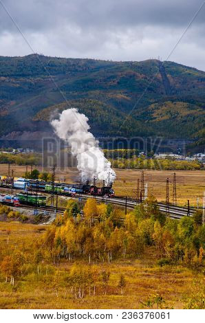 Old Steam Locomotive In The Circum-baikal Railway With Smoke In Cloudy Wearther Autumn