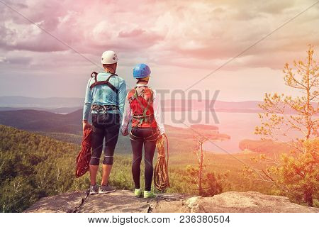 A Couple Of Climbers With Ropes On A Cliff Top. Mountain Climbing Equipment
