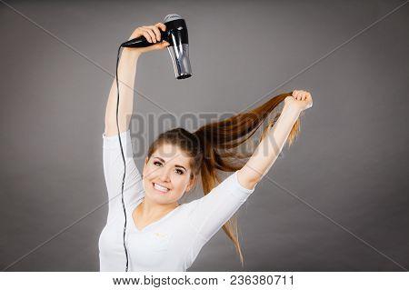 Woman Drying Her Dark Brown Hair Using Hair Dryer. Studio Shot On Grey Background.