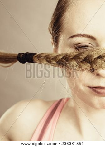 Young Woman Covering Her Mouth With Blonde Hair Braid. Haircare And Hairstyling Concept.