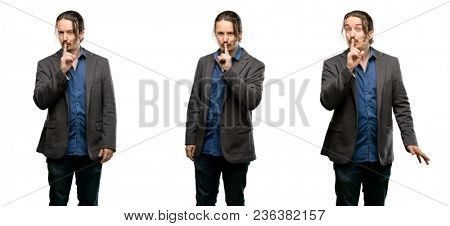 Handsome young man with index finger on lips, ask to be quiet. Silence and secret concept