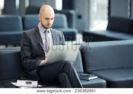 Serious businessman browsing in the net while waiting for departure in airport lounge