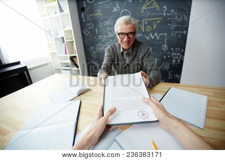 Happy mature teacher giving back paper with excellent essay to one of students after checking