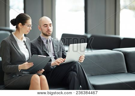 Two young delegates or agents sitting in airport lobby and discussing working moments while preparing for conference