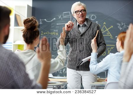 Mature teacher answering questions of his students after explanation of new subject