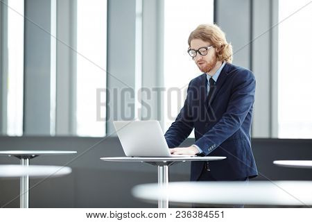 Businessman in suit and eyeglasses looking at laptop display in front in lounge of airport