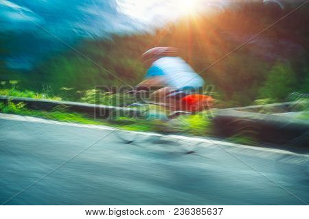 Slow motion photo of a sportsman riding on the bicycle along the mountainous road in Alps, almost on the finish line, athletic summer sport