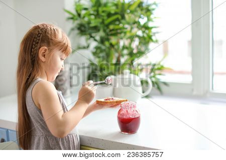 Cute little girl spreading jam on toast at home