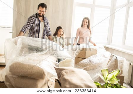 Beautiful And Friendly Family Are Unpacking Their Stuff. They Are Putting Off The Cover Of Boxes. Th