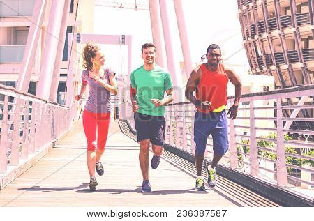 Multiethnic Runners On Urban Background - Group Of Multiracial Friends Jogging In City At Spring Tim