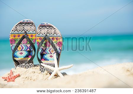 Close Up Sandals On The Sand Beach With Starfish Sandy Beach. Summer And Holiday Concept