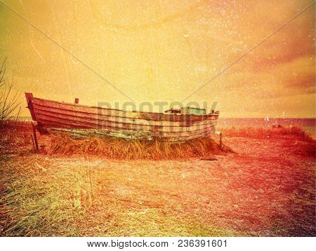 Abstract Effect.  Abandoned Fishing Boat On Bank Of Sea. Morning Silent Bay Within Windless. Dramati