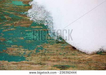 Old Wooden Plank Background With Snow And Peeling Green Paint With Selective Focus.